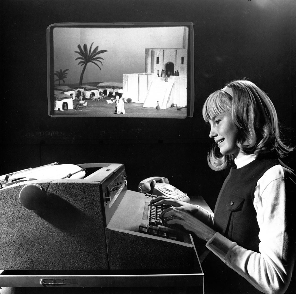 An unnamed girl sitting at a large typewriter playing The Sumerian Game with a slide projection screen in the background