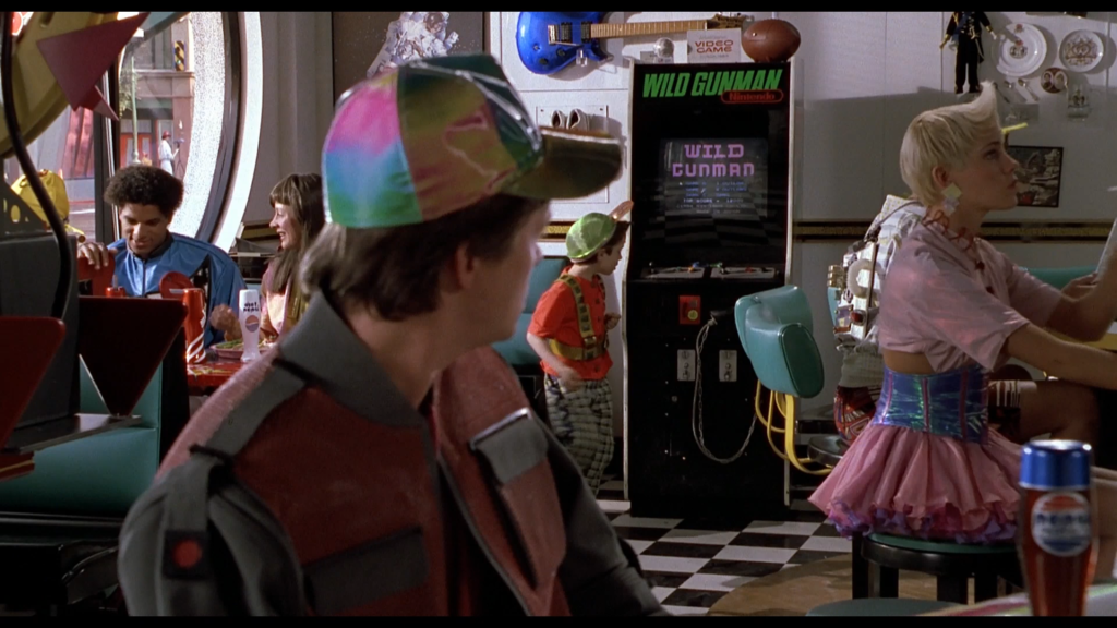 Marty McFly in a Cafe '80s in the future looks at a vintage arcade cabinet. The marquee says Wild Gunman, Nintendo.